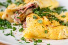 Fluffig äggomelett med skinka och ost, gräslök royaltyfria bilder