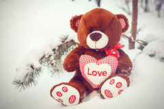 Fluffig gullig mjuk leksaknallebjörn med hjärtaförälskelse i snö Arkivfoton