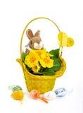 Fluffig kaninkorg med gulingblommor och spridda påskägg Arkivbilder