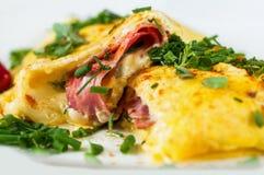 Fluffig omelett för välfyllt ägg med skinka, ost och gräsplanörten, closeup royaltyfria foton