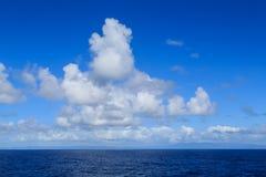 Fluffig vit fördunklar över det stillsamma havet arkivfoto