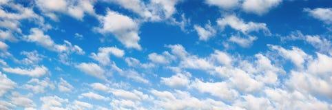 Fluffig vit fördunklar på panorama för blå himmel Arkivfoto