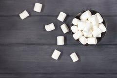 Fluffig vit marshmallow i rund bunke på svarta trätabellwi Arkivbild