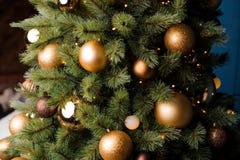 Fluffiga filialer av julgranen dekorerade med glass bollar och girlander Arkivbilder