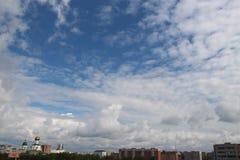 Fluffiga moln över staden Arkivbild