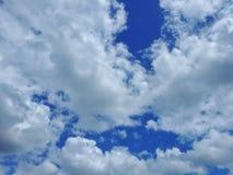 Fluffiga moln på en blå himmel arkivbilder
