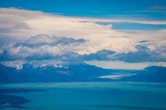 Fluffiga moln svävar över fjärden och bergen Shevelev Arkivbilder