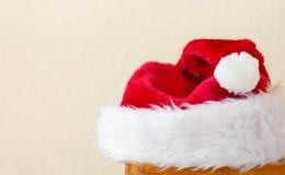 Fluffiga Santa Claus Hat som ligger på vit väggbakgrund för trästol Baner för affisch för nya år för jul med kopieringsutrymme royaltyfri bild