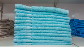 Fluffy bathing towels in blue and cyan colors stacked on shelf for sale in a store. Fluffy new towels in blue and cyan colors stacked on shelf for sale in a Royalty Free Stock Images