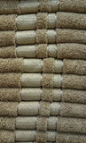 Fluffy bathing towels in brown color stacked on shelves for sale in a store Royalty Free Stock Images