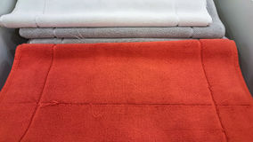 Fluffy bathing towels in red, gray and white colors stacked on shelf for sale in a store Royalty Free Stock Images