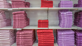 Fluffy bathing towels in red, purple and pink colors stacked on Stock Images