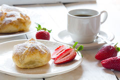 Fluffy bun of puff pastry with strawberry filling and coffee Royalty Free Stock Photos