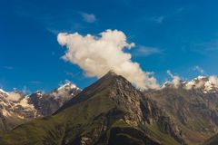 Fluffy cloud floats over mountain peak. royalty free stock image