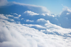 Fluffy clouds from above. Fluffy clouds on blue sky seen from above in fog Stock Image