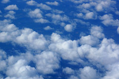 Fluffy Clouds above lands mass Stock Photo