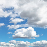 Fluffy clouds in blue afternoon sky Royalty Free Stock Images