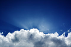Fluffy clouds blue sky crepuscular rays stock photography