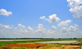 Fluffy Clouds, Blue Sky, Land and Water Stock Photos