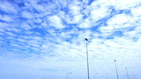 Fluffy clouds in the blue sky and the light pole lined Royalty Free Stock Images