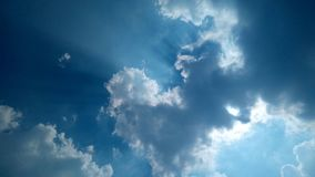 Fluffy clouds on clear blue sky. Bright blue sky with fluffy cloud and sun beam stock image