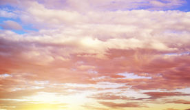 Fluffy clouds floating over the sunset sky Royalty Free Stock Photo