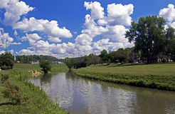 Fluffy clouds hang over the Galena River in Galena Illinois Stock Images
