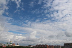 Fluffy clouds over the city Stock Photography