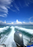 Fluffy clouds over the ocean and waves of the ship. Royalty Free Stock Images