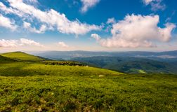 Fluffy clouds rolling above the mountain meadow. Beautiful landscape on high altitude in summer Stock Image