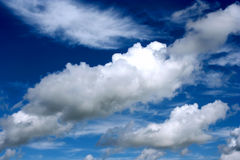 Fluffy clouds in vast blue sky Stock Photo