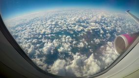 Fluffy clouds viewed from airplane windows, wing and turbine in shot, low cost stock video footage