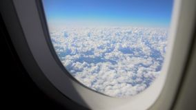 Fluffy cloudscape viewed from moving airplane window, itchy feet, wanderlust