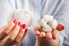 Fluffy cotton ball and cotton swabs and pads in hands royalty free stock photo