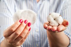 Fluffy cotton ball and cotton swabs and pads in hands royalty free stock photography
