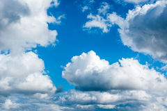Fluffy cumulus clouds in blue sky Stock Photography
