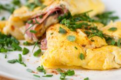 Fluffy egg omelette with ham and cheese, chive. Fluffy egg omelette stuffed with ham and cheese sprinkled with green chive, closeup royalty free stock images