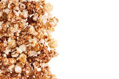 Fluffy flakes popcorn with chocolate sauce as decorative border, copy space, isolated on white background. Fluffy flakes popcorn with chocolate sauce as Royalty Free Stock Photography