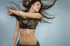 Fluffy Hair. A sexy young model moving her hair to show the motion of her fluffy long hair, in a studio Stock Photography