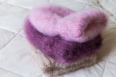 Fluffy hats of various styles and colors hand-knitted Stock Photos