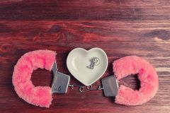 Fluffy pink handcuffs and a ceramic saucer in the shape of a heart, wherein lie the keys. On a dark wooden background Stock Photos
