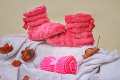 Fluffy pink home slippers and rolled scarf on knitted white blan Stock Photo