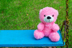 Fluffy pink teddy bear sitting on blue vintage swing Royalty Free Stock Photo
