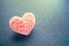 Fluffy pink thread heart on gray felt background. Handmade prett Stock Photography