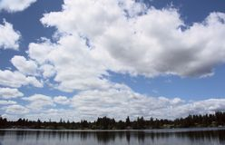 Fluffy Stratocumulus Clouds Over The Lake. Big beautiful fluffy Stratocumulus clouds  pass quietly over the lake on this perfect summer afternoon in Washington royalty free stock photo