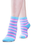 Fluffy striped socks. Woman legs in fluffy colorful striped socks ovwe white background Royalty Free Stock Image