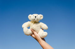 Fluffy teddy bear in hand on blue sky background Stock Image
