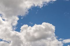 Fluffy white billowy clouds brightly back lit, blue sky. Fluffy white billowy clouds brightly back lit creating shadows and strong highlights, with a strong Royalty Free Stock Photography