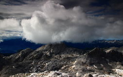 Fluffy white cloud over Hribarice plateau, Julian Alps. Fluffy white cloud over barren rocky Hribarice plateau and Debeli vrh, with Bohinj Valley,  Bohinj range Stock Images