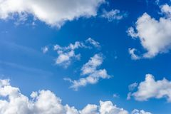 Fluffy white clouds against a bright, colorful blue sky. Beautiful fluffy white clouds of varying thickness rolling through a bright, colorful blue daytime sky stock images